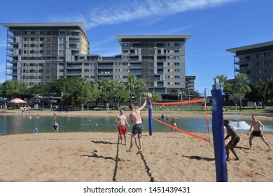 DARWIN, NT - JULY 13 2019: 2019:Australian people playing beach volleyball on man-made beach at The Darwin Waterfront Precinct, a tourist area in the Northern Territory of Australia in Darwin City.