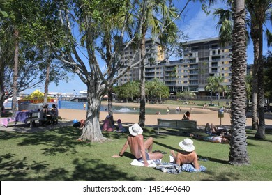 DARWIN, NT - JULY 13 2019: 2019:Australian people sunbathing onMan-made beach at Darwin Waterfront Precinct, a tourist area in the Northern Territory of Australia in Darwin City.