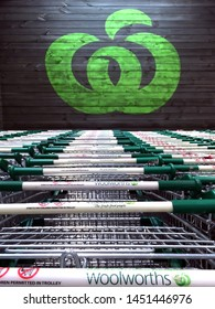 DARWIN,NT - JUNE 30 2019:Woolworths Supermarkets logo sign with shopping trolleys.Woolworths and Coles forms a near-duopoly of Australian supermarkets accounting for about 80% of the Australian market