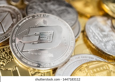 Dash physical coin on the stack of other different cryptocurrencies. Close-up photo of dash with shallow depth of field