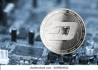 dash silver coin on blue motherboard chip digital mining computer hardware crypto currency financial background concept