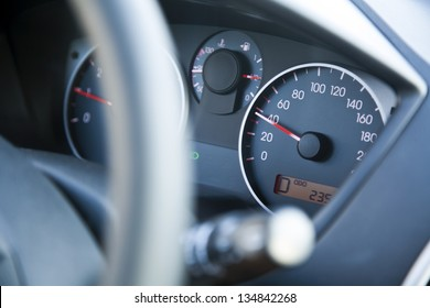 The dashboard of car going 40, within speed limits. Very shallow depth of field.