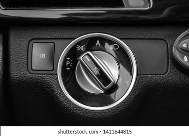 The dashboard of the car's interior is black with a dipped headlamp switch and side lights with a light sensor and automatic dimming and fog light button. Auto service industry.