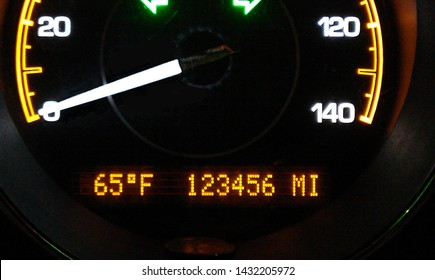 Dashboard gauge with illuminated numbers and design, with black background. Odometer displays mileage of 123456
