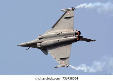 Dassault Rafale fighter jet flying with smoke trails.