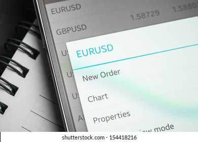 Data analyzing in forex market: the charts and quotes on smartphone display. Analytics  pair U.S. dollar  Euro.