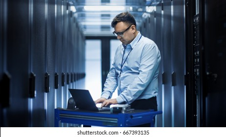 In Data Center IT Engineer Works on Crash Cart Laptop. We See Rows of Server Racks and One Cabinet is Open.