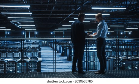 Data Center IT Specialist and e-Business Enrepreneur Talk, Use Laptop. Two Information Technology Professionals Walking on Bridge Overlooking Cloud Computing Server Farm.