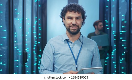 Data center specialist working on digital tablet in high tech server room. Handsome cheerful technician smiling at camera coworking in computer security.