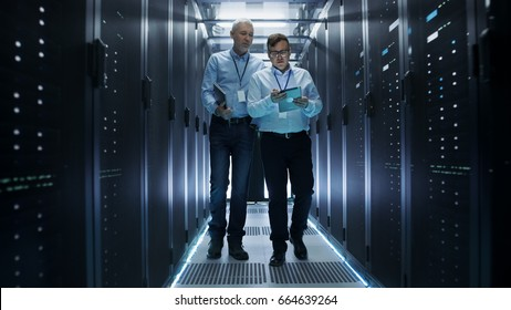 In Data Center Two IT Engineers Walking Through Rows of Server Racks. They Work on Tablet Computer and Laptop.