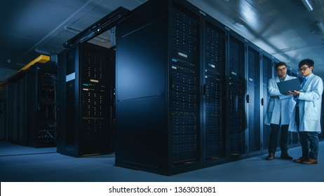 In the Data Center: Two IT Specialists Wearing White Lab Coats, Have Discussion about Working of Server Racks. Optimizing Work of Database. Cloud Computing, Artificial Intelligence Networking
