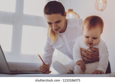 Data corrections. Financial director on maternity leave feeling occupied while correcting her business data hugging her little daughter