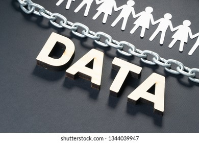 DATA letters with human paper figures and metal chain on black background. Personal data protection concept.
