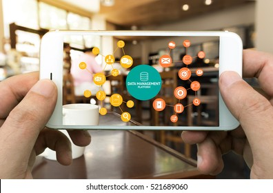 Data Management Platform (DMP) , Marketing and crm concept. Hand holding mobile phone , infographic , texts and icons on coffee retail shop background.