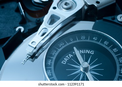 Data mining concept. Hard disk drive and compass. Compass needle point at data mining.