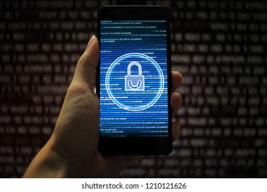 data privacy. surfing through hostile internet and hackers probe and bad government surveillance. blue padlock on mobile device on panel of red code led screen. hand holding smart phone.