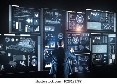 Database administrator. Calm clever database administrator feeling responsible for the working process while standing in front of a big futuristic device and analyzing the information