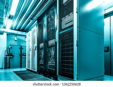 Datacenter server racks with network computers in neon blue toning. Room with several of mainframe hardware and supercomputers in big modern data center