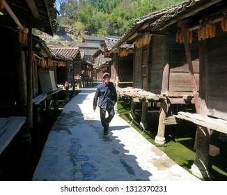 Datang, China - March 8, 2018: A Chinese man walking down a traditional village street lined by old granaries