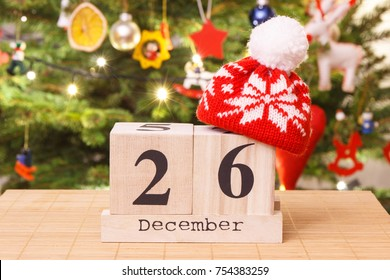 Date 26 December with woolen red cap and festive tree with lights and decoration in background, Christmas time concept