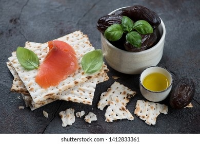Date fruits, matzo bread, salmon fillet and green basil over grey stone background, horizontal shot