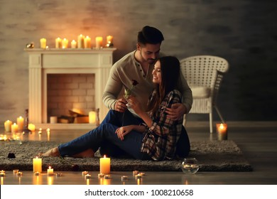 Date of happy young couple in room with burning candles
