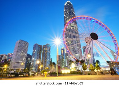 Date: July 28, 2018: Focus on Hong Kong observation wheel surrounding with many business buildings with beautiful lights at night, Hong Kong landmark and cityscape, located in Hong Kong city