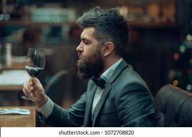 Date meeting of hipster awaiting in pub. Perfect wine. bar customer sit in cafe drinking alcohol. Businessman with long beard drink in cigar club. Bearded man rest in restaurant with wine glass.