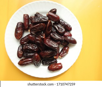 date palm fruits in a plate, top view, dry sweet fruits for iftar in ramadan time