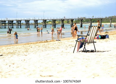 Dated 13 Jan 2018. People at beach on hot summer day. Beach in Australia, Jetty beach Coffs Harbour. Day time image of chair on beach sand, ocean, swimmers, jetty, blue sky in background.