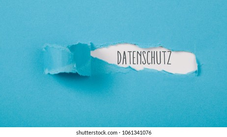 Datenschutz (German for data protection/privacy) message on torn blue paper revealing secret behind ripped opening.