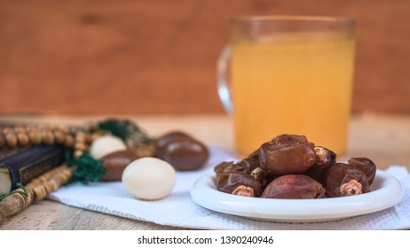 Date-palm in white plate with orange juice, small quran and rosary placed on wooden background. Simple iftar food set for Ramadan break fasting.