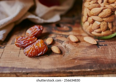 Dates and almonds on a wooden background