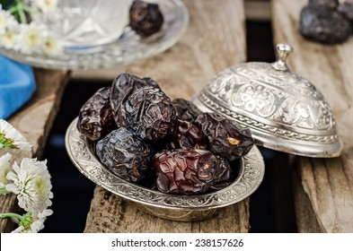 Dates in arabian iron bowl on wooden background