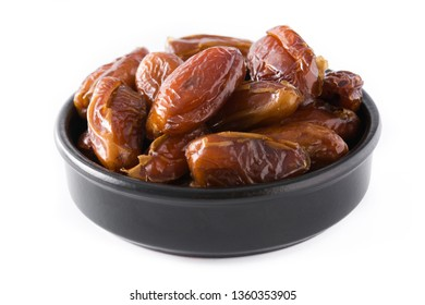 Dates in black bowl isolated on white background. Copyspace