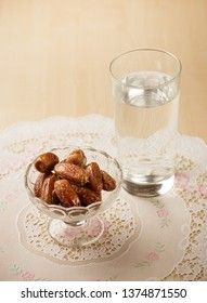 Dates - a blessed fruit to consume while breaking Ramadan fast. Bowl of dates and a glass of pure drinking water.
