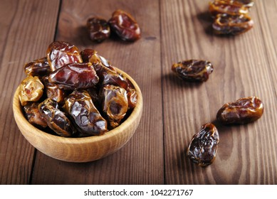 Dates in a bowl on a dark wooden background.