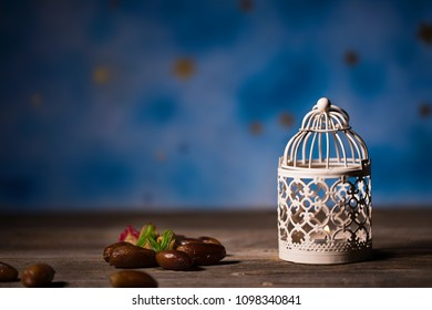 Dates and candle holder on a wooden surface. Closeup