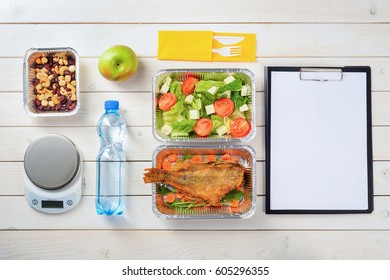 Dates, cashews and hazelnuts, fish with sliced carrot, lettuce, tomato and feta salad, an apple, plastic cutlery, a bottle of water, a kitchen scale and note paper. Diet food delivery.