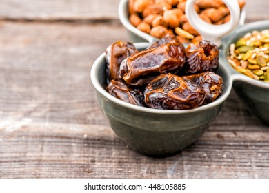 Dates fruit in a ceramic bowl with almonds and pumpkin seed closeup on wooden background,  Raw Organic Medjool Dates Ready to Eat. Medjool The perfect date, Natural Sweetener, healthy dried fruits.