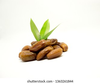 Dates are the fruit of the date palm tree, which is grown in many tropical regions of the world. these are dried dates with leaves on white background