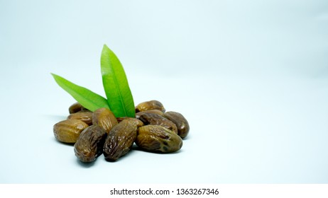Dates are the fruit of the date palm tree, which is grown in many tropical regions of the world. These dried dates with leaves isolated on white background
