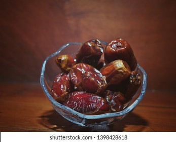 Dates fruits or Kurma in bowl isolated on wood background