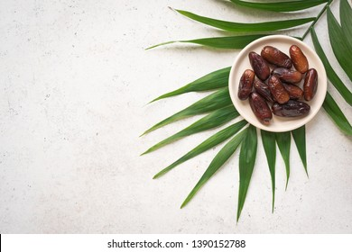 Dates fruits on plate on white background, top view, copy space. Organic dried dates fruits.