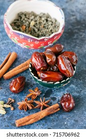 Dates, green tea and spices cardamom, anise stars, cinnamon sticks, cloves, on a blue stone background.