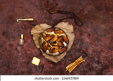 dates on plate above heart shape from leaves holy book of muslims and rosary, siwak, perfume on pink background
