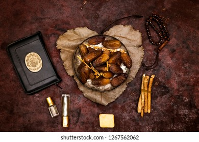 dates on plate above heart shape from leaves holy book of muslims and rosary, siwak, perfume, holy book of muslim