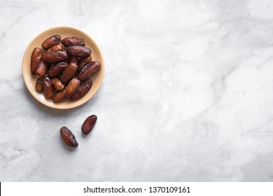 Dates on plate on white marble background, top view, copy space. Organic dried dates fruits.