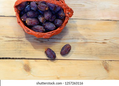 Dates on a wooden table in a wicker basket.