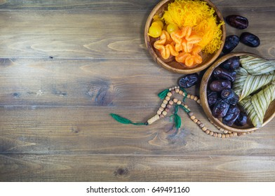Dates palm on wooden plate with dessert,ketupat and wooden rosary on dark wood backgrounds. Selective focus. Top view.